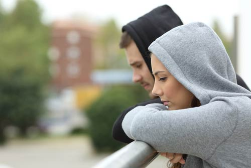 Two people in hoodies looking over a balcony
