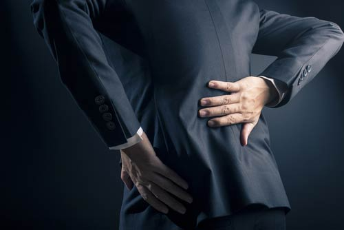 Man in suit with back pain