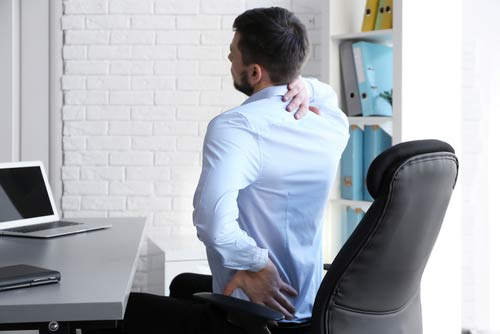 Man grabbing his backbecause of discomfort