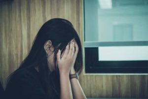 Sad young woman covering her face