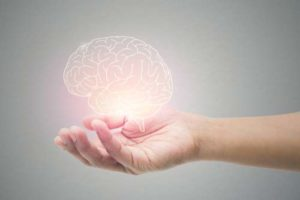 A glowing brain hovering over a hand