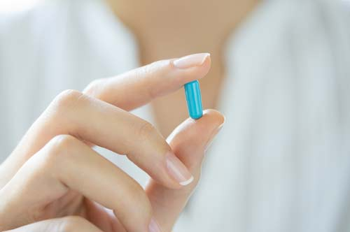 A blue pill in a woman's hand