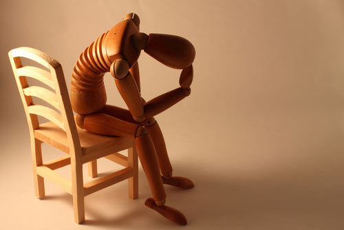 Melancholy wooden figure on a wooden chair